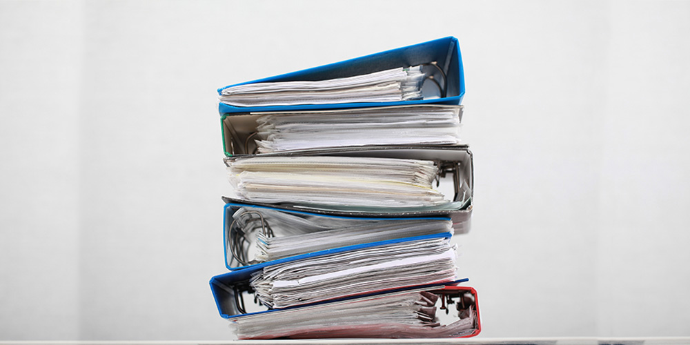 A teetering stack of medical QMS files